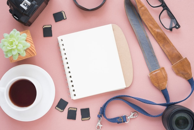 Cup of a tea; blank spiral notepad; succulent plant; camera; memory cards; camera lens; spectacle and belt over pink background