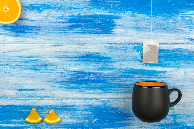 The cup of tea on a blue background. tea bag and orange slices