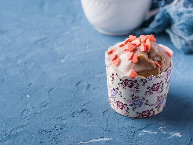 Cup of tea on blue background with frosted cupcake, flowers and textile
