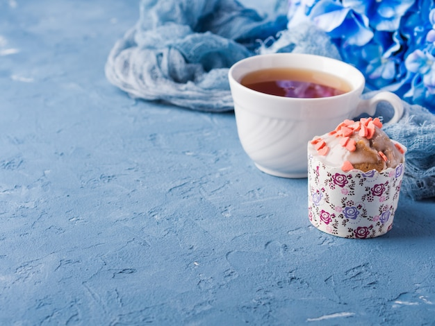 Cup of tea on blue with frosted cup cake, flowers and textile