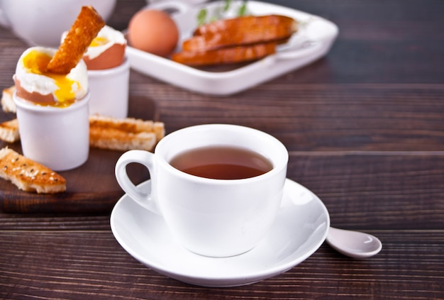 Cup of tea and boiled egg in eggcup on wooden board with crispy toast.