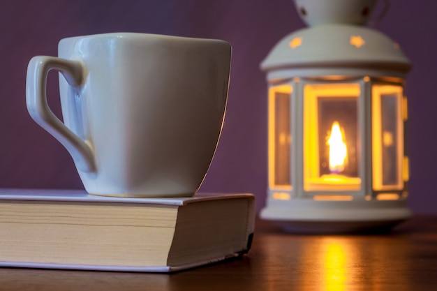A cup of tea on a book in the light of a lantern with a candle