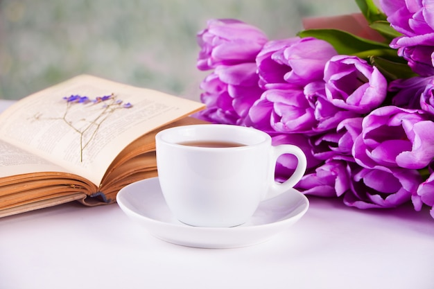 A cup of tea, book and violet tulips on the table