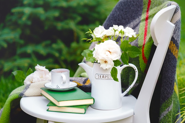 Cup of tea on books, flowers white wild rose in vase teapot, warm plaid on white chair outside in summer garden.