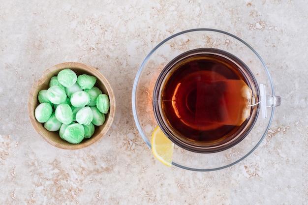 Una tazza di tè e una ciotola di caramelle alla menta