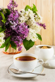 Cup of tea and branch of lilac flower in wicker basket on linen tablecloth