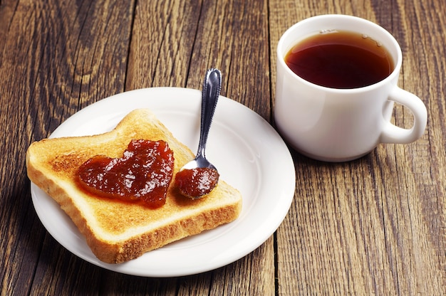 Cup of tea and bread with jam in the shape of heart