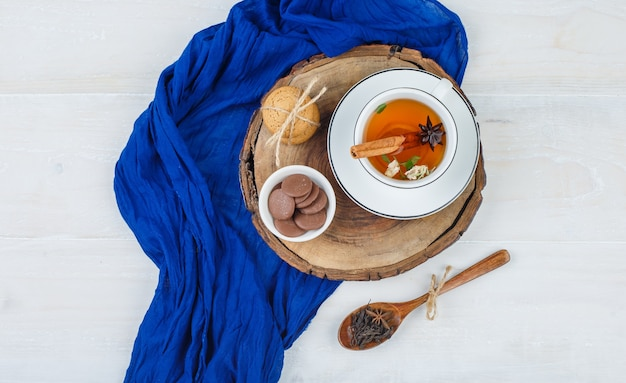 Cup of tea, brown and white cookies on wooden board with blue scarf and a spoon of cloves