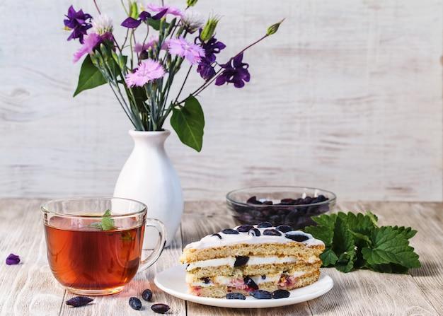 カップティー、皿の上のケーキと木製のテーブルの上の花の花束