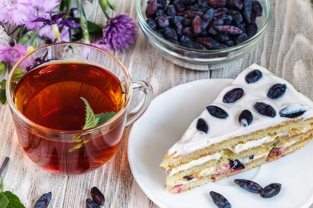 カップ茶、木製のテーブルの上の皿の上のケーキ