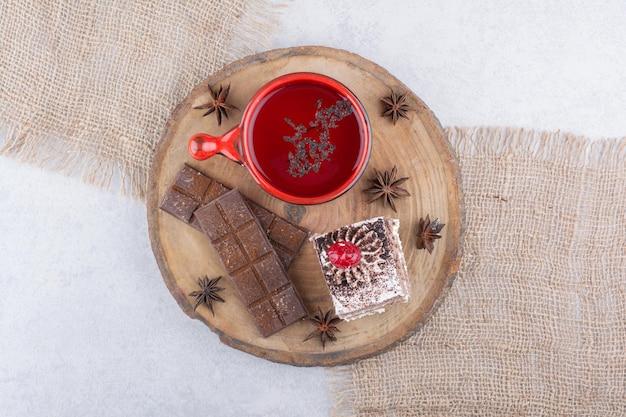 Tazza di tè, fetta di torta e barretta di cioccolato su un pezzo di legno. foto di alta qualità