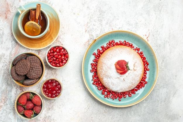 Una tazza di torta da tè ai frutti di bosco una tazza di tè ciotole di biscotti alla marmellata di frutti di bosco