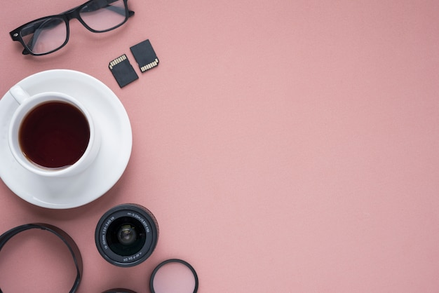 Cup of tea; camera lens; spectacle; memory cards and extension rings over colored pink
