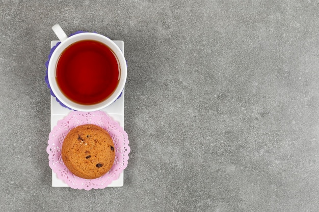 Cup of tea and chip cookies on white saucer