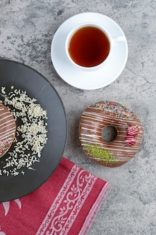 Cup of tea and chocolate donuts with berry and sprinkles on marble surface.