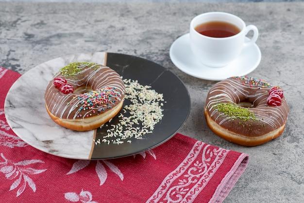 Tazza di tè e ciambelle al cioccolato con frutti di bosco e spruzza sulla superficie in marmo.