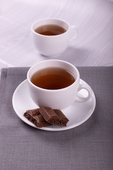 Cup of tea and chocolate with light background