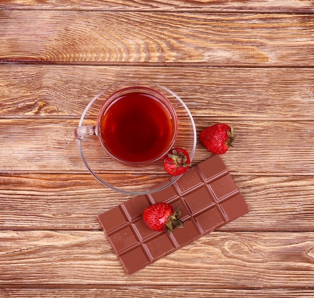 A cup of tea or coffee. dark chocolate. wooden background.