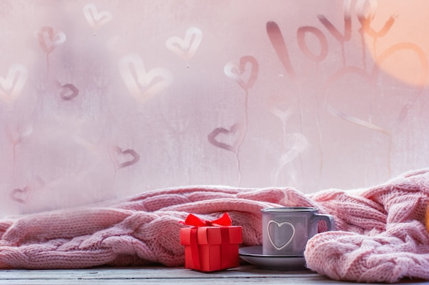 Cup of tea, coffee or hot chocolate and pink plaid on foggy window with love text. valentine day and love concept.