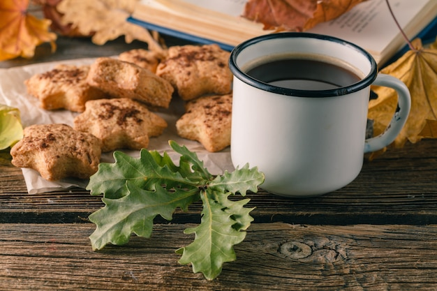Cup tea or coffee with autumn leaves and cookies. seasonal, tea time, still life concept.