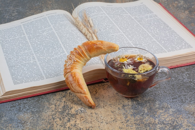 Tazza di tè, biscotto e libro sulla superficie di marmo