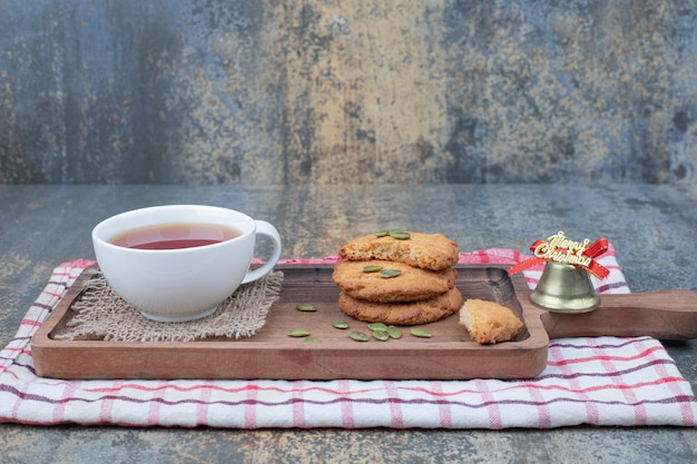 Cup of tea, cookies and christmas beel on wooden board. high quality photo