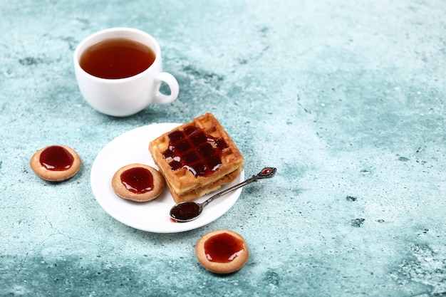 A cup of tea, cookies and waffle with strawberry jam.