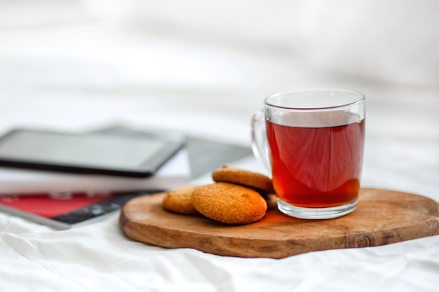 A cup of tea, cookies on a wooden surface.
