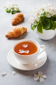 Cup of tea and croissant on gray