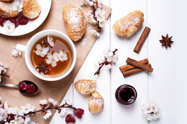 Cup of tea, croissants and spring flowering branches on a white wooden background. flat lay style