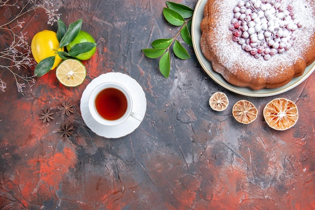 A cup of tea a cup of black tea citrus fruits cake with berries star anise