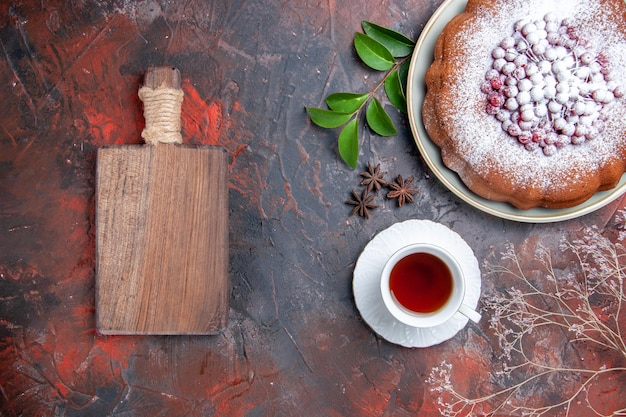 A cup of tea a cup of tea a cake with berries leaves the wooden cutting board