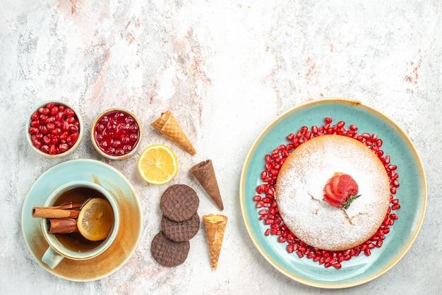 Una tazza di tè una tazza di tè cannella limone la torta con fragole e biscotti