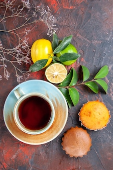 A cup of tea cupcakes a cup of tea citrus fruits leaves on the red-blue table