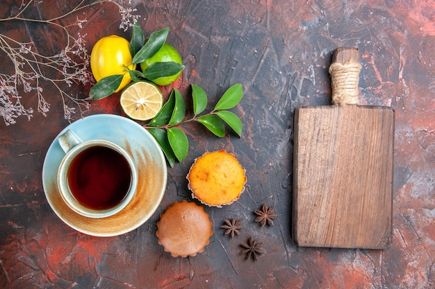 A cup of tea cupcakes a cup of tea lemons limes star anise the cutting board