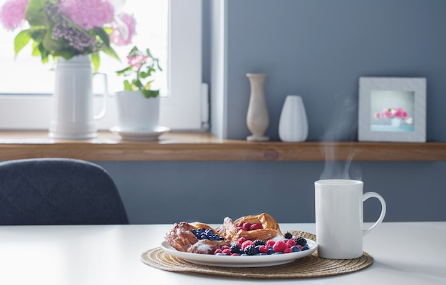 Cup of tea  and  danish with berries  on  white table