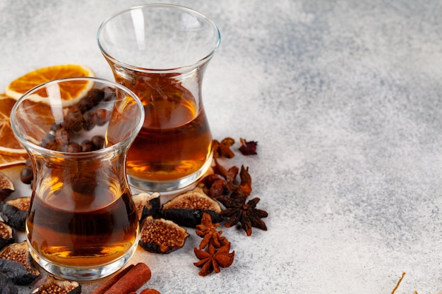 Cup of tea decorated with pieces of dried orange and fig