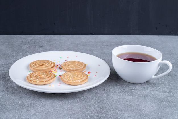 Tazza di tè e biscotti deliziosi sul piatto bianco