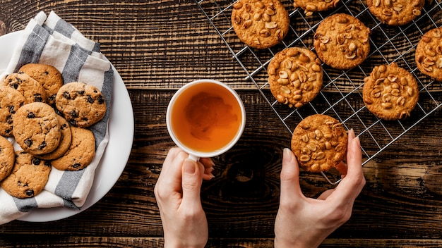 Cup of tea and delicious cookies on table