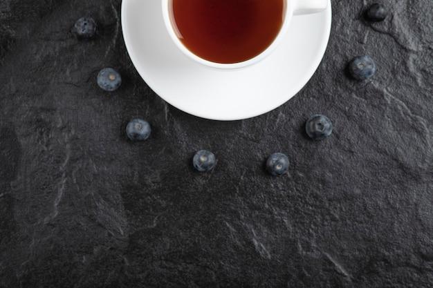 Tazza di tè e deliziosi mirtilli freschi su superficie nera