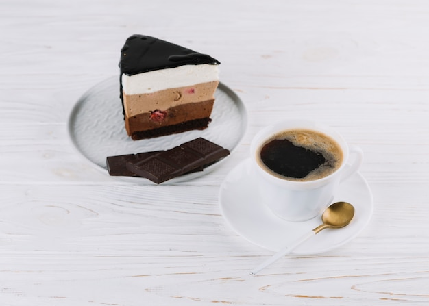 Cup of tea; delicious pastry with chocolate bar for breakfast on wooden table