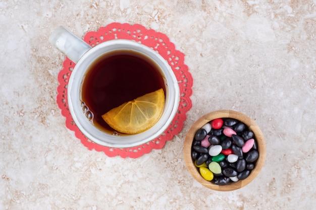 Una tazza di tè su un centrino e una porzione di caramelle assortite