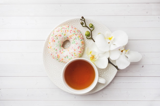 Cup of tea and donuts, white orchid on white table with copy space. flat lay, top view.