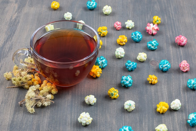 Cup of tea, dried flowers and colorful popcorn on wooden surface