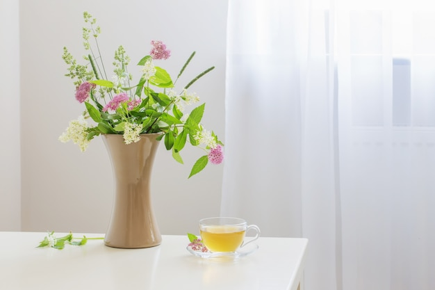 Cup of tea and flovers on table at home