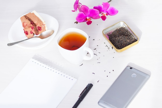 Cup of tea, flowers, spiral notepad, pen. time management, new day planning concept.