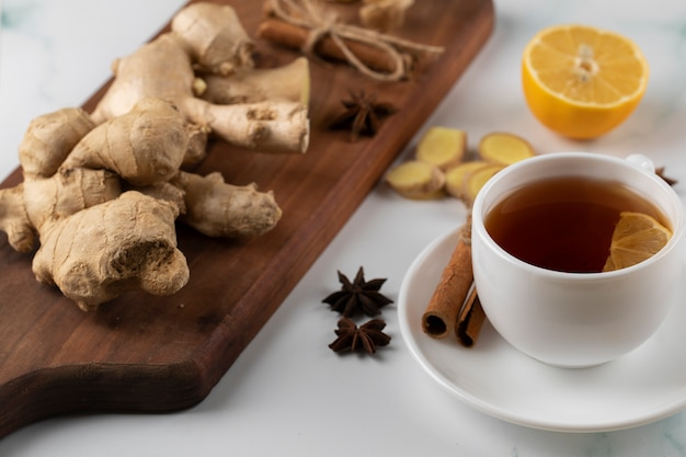 A cup of tea and ginger plants on a wooden board.