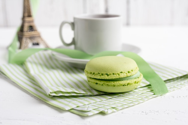 Cup of tea and green french macaroons on a white wooden