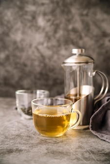 Cup of tea and grinder on marble background