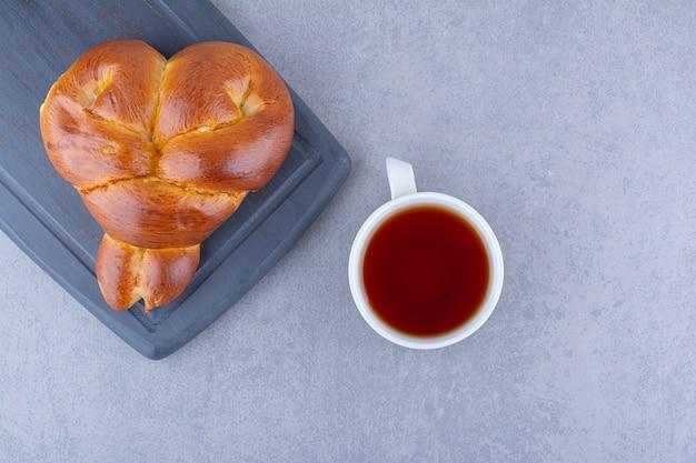 Una tazza di tè e un panino dolce a forma di cuore su un bordo blu marino su una superficie di marmo